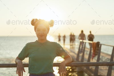 Portrait of confident young woman leaning on railing at pier over sea