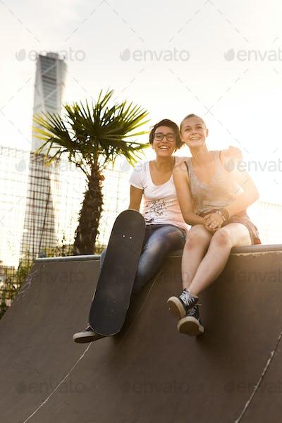 Full length of happy female friends sitting at edge of skateboard ramp