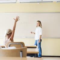 Elementary student raising hand in math class