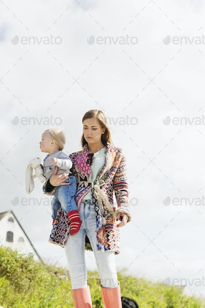 Low angle view of mother holding son on grassy field against clear sky
