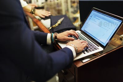Midsection of salesman using laptop in showroom