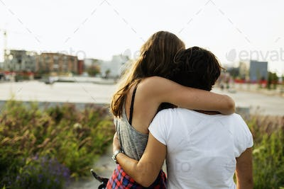 Rear view of female friends embracing at skateboard park