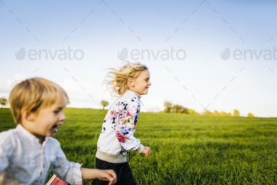Cheerful siblings running on grassy field against clear sky