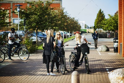 Happy female friends with bicycles standing at college campus