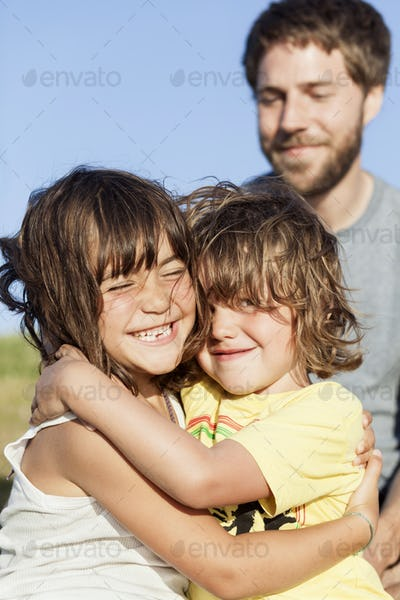 Cute boy embracing sister while father looking at them in park