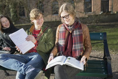 Smiling teenage friends studying in college campus