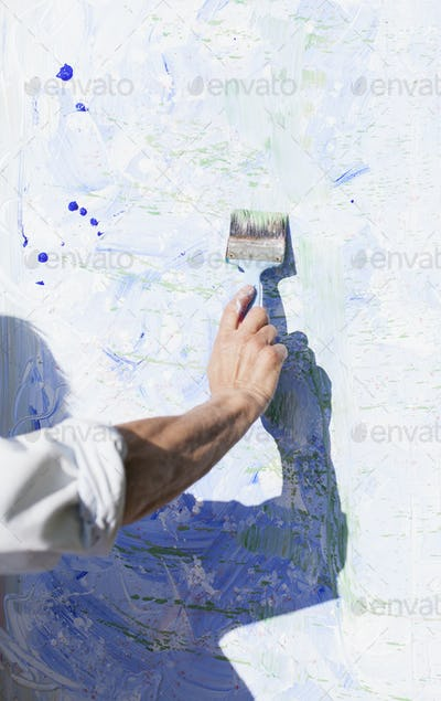 Cropped image of senior female artist painting canvas outdoors