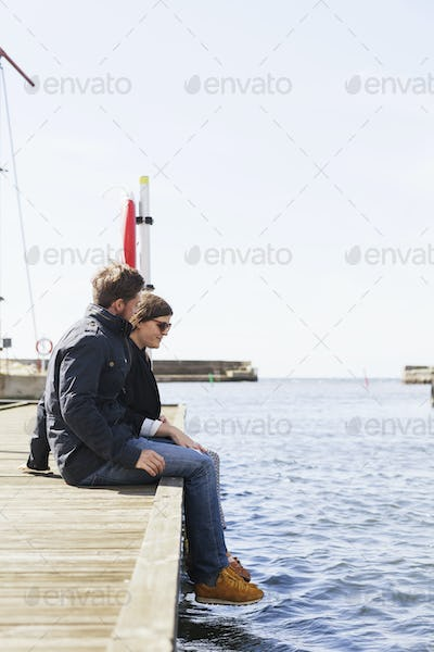 Couple sitting on pier at harbor against clear sky