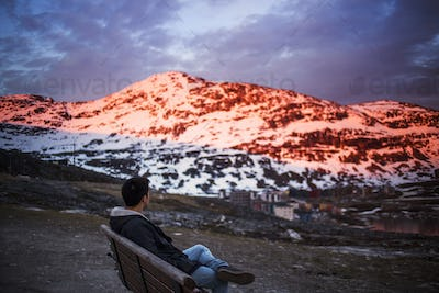 Side view of young man relaxing on bench with snow covered mountain in background