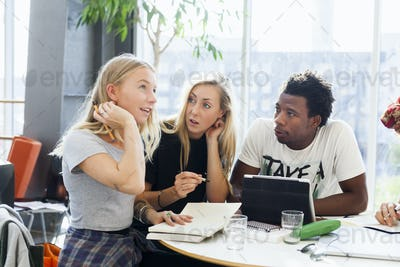 Multi-ethnic college students looking at thoughtful friend while studying at cafe table