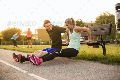 Smiling man and woman talking while stretching on wooden bench at park