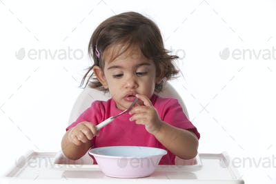 Curious baby girl is testing her fork