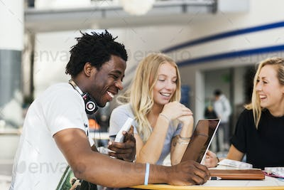 Happy multiethnic friends studying at table in cafe