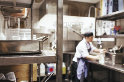 Close-up of shelf with chef working in background at commercial kitchen counter