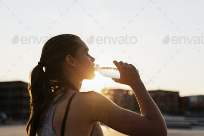 Side view of woman drinking water at skate park during sunset