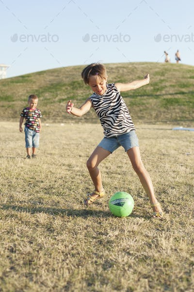 Little girl kicking ball while brother looking at her on grassy field