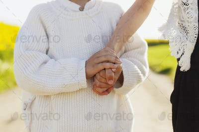 Midsection of boy holding sister's hand on field