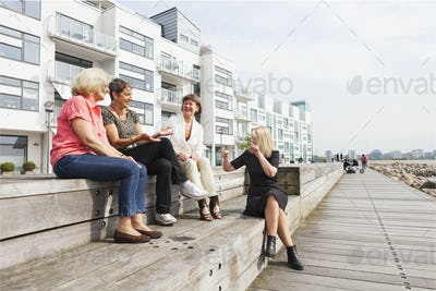 Full length of happy female friends talking on floorboard at seaside