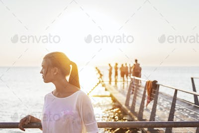 Young woman standing by railing on pier over sea