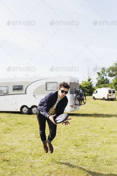Man holding plastic disc on grassy field against clear sky