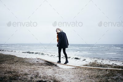 Full length rear view of young woman balancing on wood at beach