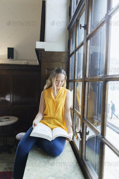 Young woman reading book while sitting on window sill at cafe