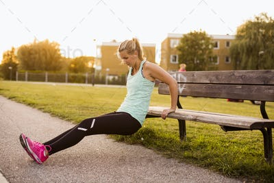 Determined woman stretching on wooden bench at park