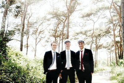 Portrait of happy male graduates standing at university park