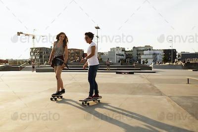Two female skateboarders riding in skate park