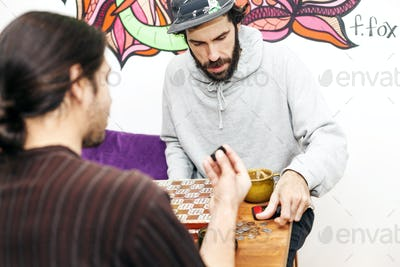 Male friends playing board game at cafe