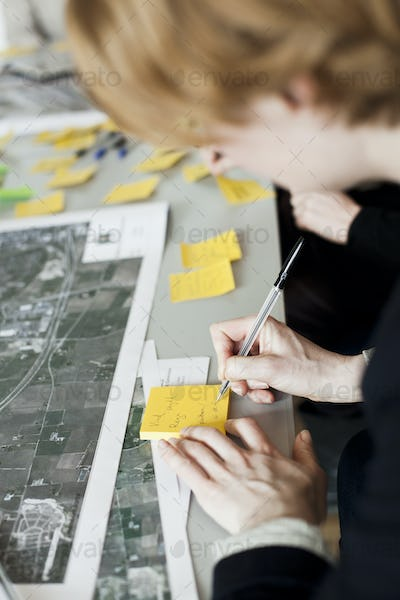 Cropped image of businessman writing on adhesive note in office