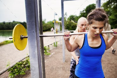 Woman helping friend in lifting barbell at park