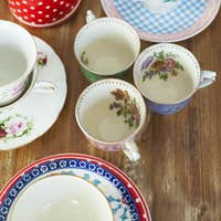Variety of tea cups and saucers on wooden table