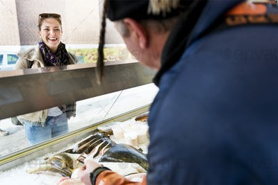 Smiling female customer looking at fisherman in store
