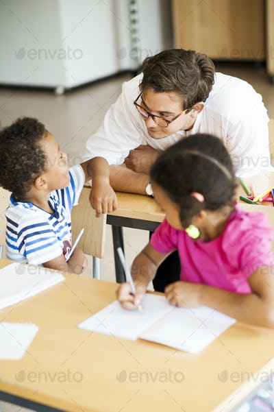 Boy talking with teacher in classroom