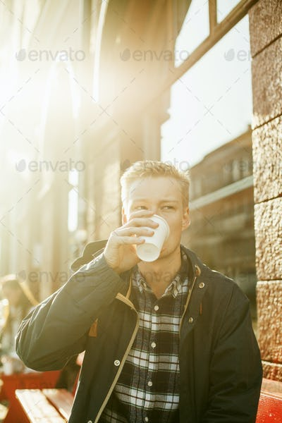 Businessman looking away while drinking coffee outside cafe
