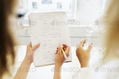 Cropped image of female students analyzing formulas while performing experiments in classroom