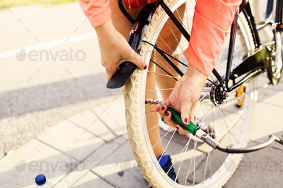 Low section of sporty woman inflating bicycle tire at park
