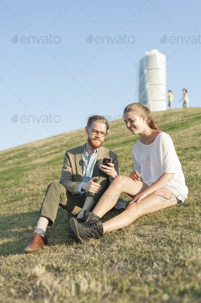 Happy couple using cell phone sitting on grassy hill in city