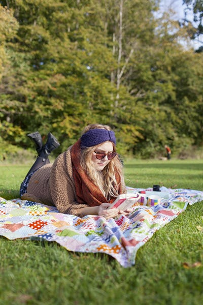 Full length of young woman reading novel while lying on picnic blanket at forest