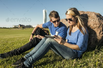 Couple using digital tablet at park with Turning Torso skyscraper in background