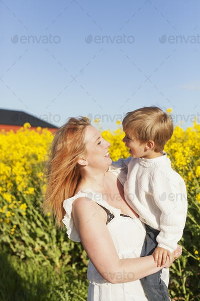Happy woman carrying son at oilseed rape field
