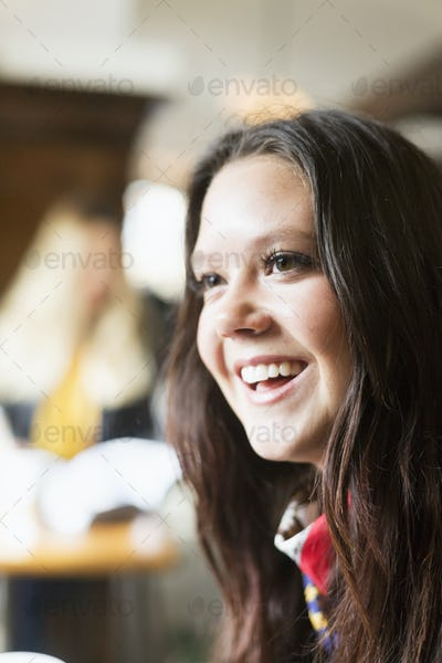 Happy young woman looking away in station cafe