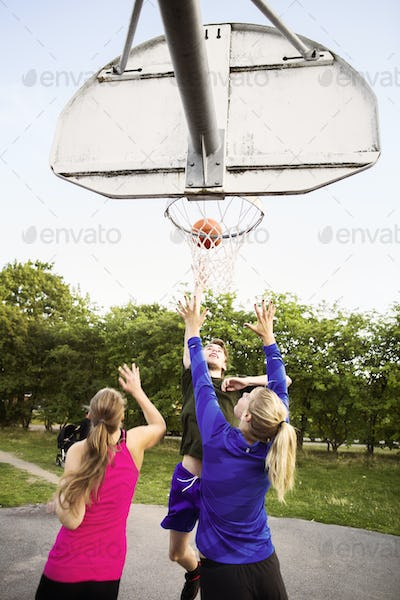 Male and female friends playing basketball at park