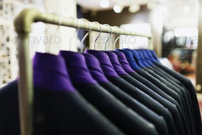 Row of suits hanging on rack in clothing store