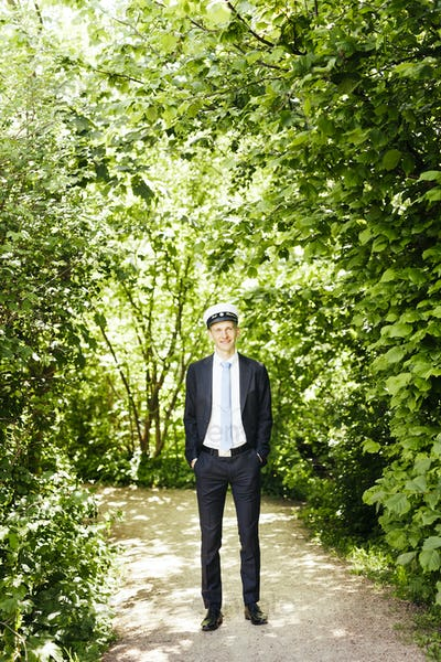 Thoughtful male graduate standing with hands in pockets against trees
