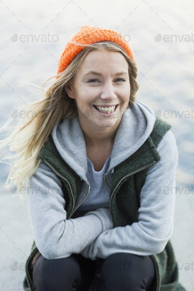 Portrait of happy female student sitting on retaining wall against river