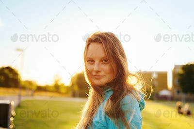 Portrait of confident sporty woman at park during sunset