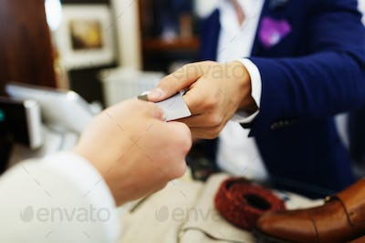 Cropped hands of customer giving credit card to cashier in clothing showroom