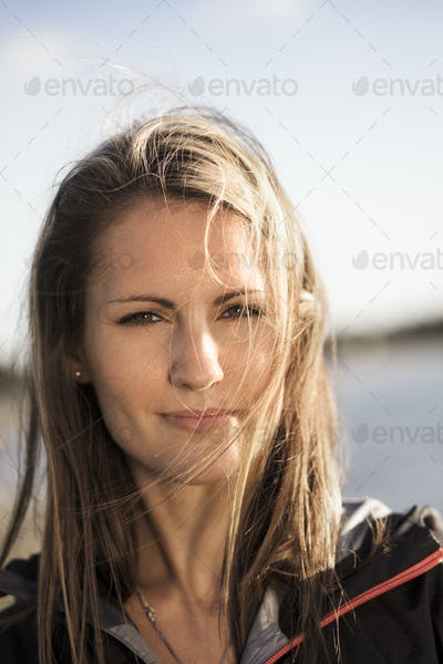 Close-up portrait of woman by lake against sky on sunny day